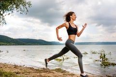 Uma mulher desportiva bonita que corre na costa de um lago nos esportes fotografia de stock