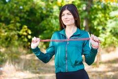 Uma mulher desportiva nova com a corda de salto que faz os exercícios exteriores fotos de stock
