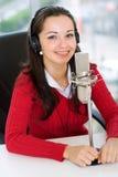 Uma mulher DJ é na frente de um mic Fotos de Stock