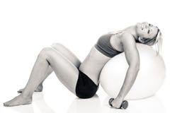 Uma mulher do ajuste cansado após ter feito uma rotina em uma bola vermelha do exercício Imagem de Stock Royalty Free