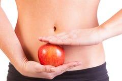 Uma mulher do ajuste e uma maçã vermelha Imagens de Stock Royalty Free