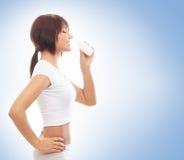 Uma mulher do ajuste na água potável desportiva branca da roupa imagens de stock