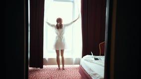 Uma mulher do gengibre no roupão abre as cortinas na sala de hotel e a vista na janela vídeos de arquivo