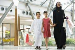Uma mulher do Oriente Médio com compra de duas crianças imagens de stock