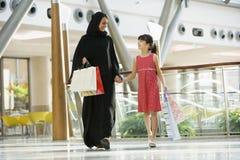 Uma mulher do Oriente Médio com uma compra da menina imagem de stock
