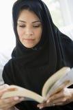 Uma mulher do Oriente Médio que lê um livro fotografia de stock