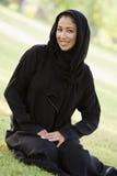 Uma mulher do Oriente Médio que senta-se em um parque foto de stock