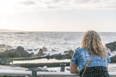 Uma mulher do turista observa o mar ao descansar em uns trilhos imagens de stock royalty free