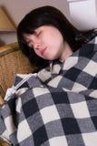Uma mulher dorme na manta coberta Imagem de Stock