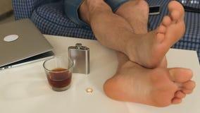 Uma mulher e um homem decolam as alianças de casamento e põem-nas sobre a tabela na tabela é o álcool, pés dos homens Close-up filme