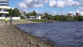 Uma mulher e um homem estão correndo no dia o litoral ou o lago, movimento lento video estoque
