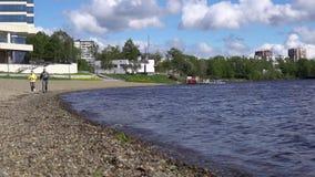Uma mulher e um homem estão correndo no dia o litoral ou o lago, movimento lento vídeos de arquivo