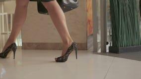 Uma mulher elegantemente vestida com um saco em sua mão escala acima a escada rolante no centro de negócios filme