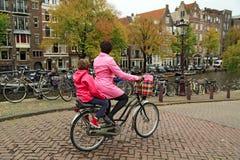 Uma mulher em uma bicicleta, levando sua criança no assento traseiro da criança Amsterdão, Países Baixos Fotografia de Stock Royalty Free
