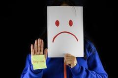 Uma mulher em uma camiseta azul que cobre e que esconde sua cara com um cartão branco com um sinal triste do desenho da cara que  imagens de stock royalty free
