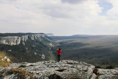Uma mulher em uma camiseta vermelha est? sobre uma montanha e fotografa uma paisagem da montanha foto de stock