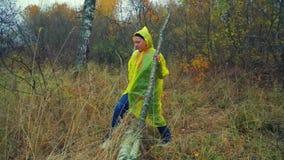 Uma mulher em etapas amarelas de uma capa de chuva sobre uma árvore caída na floresta vídeos de arquivo