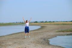 Uma mulher em uma saia azul que anda ao longo do rio Imagens de Stock