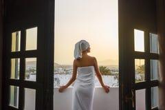 Uma mulher em uma toalha branca está estando em um terraço que negligencia as montanhas em uma sala de hotel Imagens de Stock