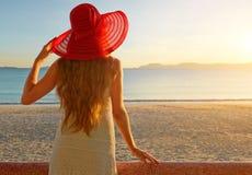 Uma mulher em um balcão que olha o por do sol bonito Imagens de Stock Royalty Free
