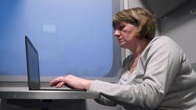 Uma mulher em um carro de trem trabalha com um portátil video estoque