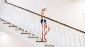 Uma mulher em um chapéu branco grande anda abaixo de uma grande escadaria branca 4K Movimento lento filme
