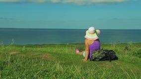 Uma mulher em um chapéu de palha com uma trouxa atrás dela para trás senta-se em uma montanha e admira-se a vista abaixo Tiro da  filme