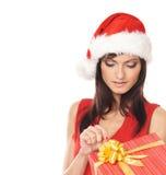 Uma mulher em um chapéu do Natal que abre um presente Imagem de Stock Royalty Free