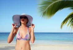 Uma mulher em um chapéu do verão olha fixamente na distância, entre o oceano Imagens de Stock Royalty Free