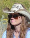 Uma mulher em um chapéu e em óculos de sol de cowboy Fotografia de Stock