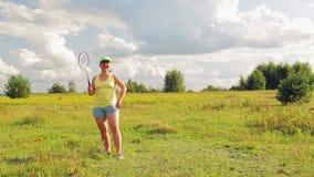 Uma mulher em um esclarecimento serve e bate a bola ao jogar o badminton filme