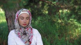 Uma mulher em um lenço muçulmano que senta-se na grama perto de uma árvore no parque filme