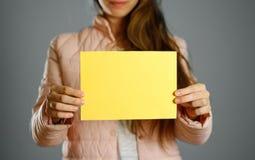Uma mulher em um revestimento morno do inverno que guarda um folheto amarelo blank fotografia de stock