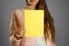 Uma mulher em um revestimento morno do inverno que guarda um folheto amarelo blank fotos de stock