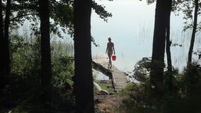 Uma mulher em um roupa de banho com uma cubeta em suas mãos está em um cais de madeira filme
