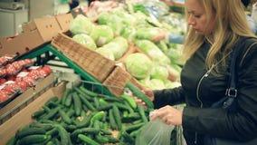 Uma mulher em um supermercado em uma prateleira vegetal, em vegetais das compras e em frutos O homem escolhe pepinos filme