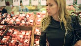 Uma mulher em um supermercado em uma prateleira vegetal, em vegetais das compras e em frutos O homem escolhe um tomate filme