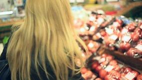 Uma mulher em um supermercado em uma prateleira vegetal, em vegetais das compras e em frutos O homem escolhe um tomate video estoque