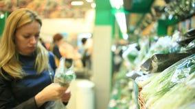 Uma mulher em um supermercado em uma prateleira vegetal, em vegetais das compras e em frutos Um homem escolhe verdes filme