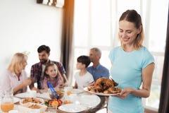 Uma mulher em um t-shirt azul está preparando-se para servir um peru cozido para o dia da ação de graças Fotos de Stock Royalty Free