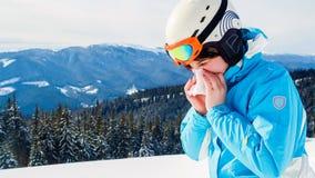 Uma mulher em um terno de esqui azul está guardando um lenço e está limpando seu nariz Esquiador com frio imagens de stock