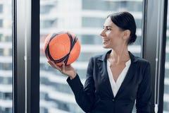Uma mulher em um terno de negócio restrito guarda um futebol alaranjado em suas mãos A parte traseira pode considerar o mar e o c Foto de Stock