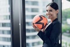 Uma mulher em um terno de negócio restrito guarda um futebol alaranjado em suas mãos A parte traseira pode considerar o mar e o c Fotos de Stock