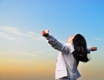 Uma mulher em um terno de negócio com suas mãos levantadas Fotografia de Stock Royalty Free