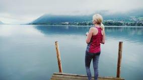 Uma mulher em um terno do esporte admira o lago alpino cedo na manhã Guarda um smartphone em sua mão tiro do steadicam video estoque