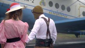 Uma mulher em um vestido cor-de-rosa acompanha um homem em um terno piloto retro do ` s a um plano de Dnepropetrovsk video estoque