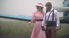 Uma mulher em um vestido cor-de-rosa e em um chapéu branco vem ao piloto no capacete que está no fundo de um vintage video estoque