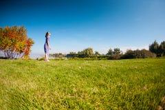 Uma mulher em um vestido está andando na grama fotos de stock royalty free