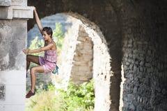 Uma mulher em um vestido está escalando uma parede de tijolo fotografia de stock royalty free