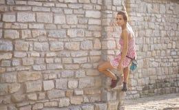 Uma mulher em um vestido está escalando uma parede de tijolo imagens de stock